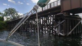 Canottaggio sul lago sotto il ponte di legno Fotografia Stock Libera da Diritti