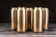 Cans of beer on wooden table. Against black background Royalty Free Stock Images