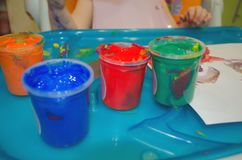 Cans with blue, orange green and red paints for children stock photos