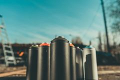 cans with colorful spray paint for graffiti on asphalt with blue sky royalty free stock photography