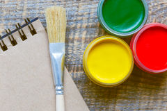 Cans gouache with brush on a wooden background Stock Photo