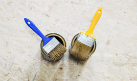 Cans of paint and brush in blue and yellow Stock Photo