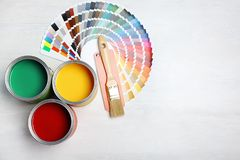 Cans with paint, brush and color palette. On light background, top view. Space for text stock photos
