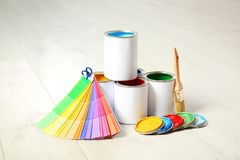 Cans of paint, brush and color palette. On wooden floor indoors stock image