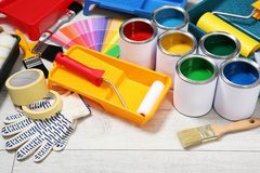 Cans of paint and decorator tools. On wooden floor stock image
