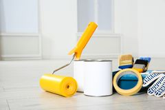 Cans of paint and decorator tools. On wooden floor indoors royalty free stock photos