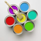 Cans of paint with paintbrush. A group of colorful paint cans with paintbrush stock photo