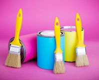 Cans of paint and paintbrush on pink background. Pastel color Royalty Free Stock Image