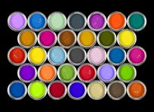 Cans of paint. 33 tins of paint/ink in a variety of colours on black background Royalty Free Stock Images