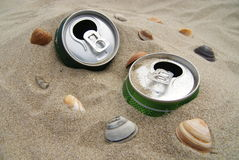 Cans in the sand. On the beach with shells Stock Image