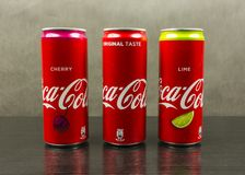 Cans with three types of Coca-Cola: original taste, lime, cherry. On a dark background. Niedomice, Poland - March 06, 2018: Cans with three types of Coca-Cola Royalty Free Stock Images
