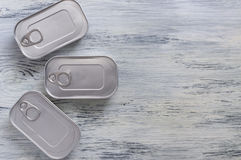 Cans on a wooden background. Three cans of canned food on a table. Stock Image