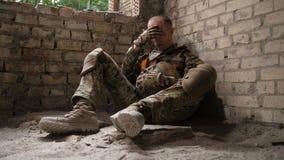 Cansado após o soldado do exército da batalha que senta-se na terra video estoque