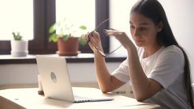 Cansado da fadiga ocular do sentimento da jovem mulher dos vidros após o trabalho do computador vídeos de arquivo