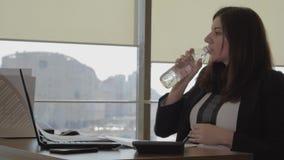 Cansado da mulher gravida do trabalho na água potável e em afagar do escritório seu estômago video estoque