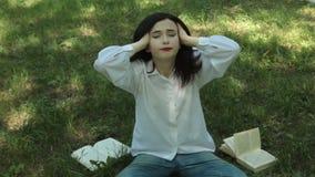 Cansado de leer el libro, la muchacha se relaja almacen de metraje de vídeo
