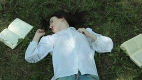 Cansado de los libros de lectura, la muchacha está durmiendo en la hierba Enfoque adentro metrajes