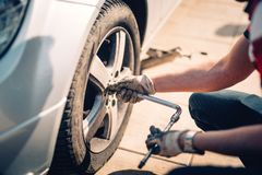 Canse el mantenimiento, el neumático dañado del coche o los neumáticos estacionales cambiantes usando la llave Cambio de un neumá imagenes de archivo