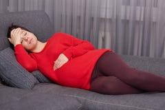 Canse a la mujer joven europea guarda una mano en el estómago y la otra encendido frente, miente en el sofá cómodo, descansa en c foto de archivo libre de regalías