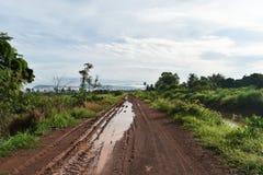 Canse la pista de muchos vehículo en el camino del fango del suelo en campo en la estación de lluvias imagen de archivo