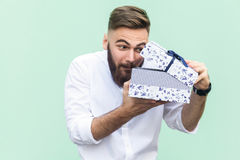 Cant stand, Its my! Curiosity young adult bearded man looking in gift box. Isolated on light green background, studio shot stock image