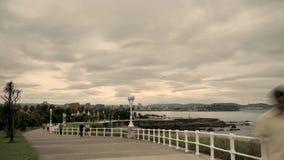 Cantabrian海海滨公园4 k timelaps温暖的日落颜色、走的人民和剧烈的快行云彩的  股票录像