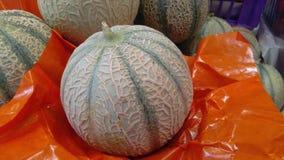 Cantaloup sur la feuille orange Images stock