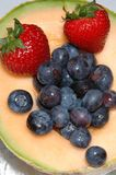 Cantaloupe, blueberries and strawberries. Cantaloupe with blueberries and two strawberries Stock Photo