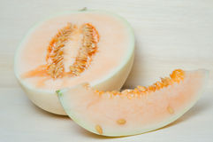 Cantaloupe or Charentais melon with half and seeds on wooden boa Stock Photo
