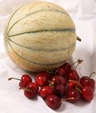Cantaloupe and cherries. Whole cantaloupe melon and red cherries Royalty Free Stock Images
