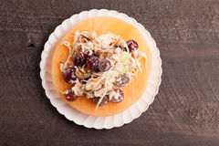 Cantaloupe with chicken grape salad on plate above view Royalty Free Stock Photography