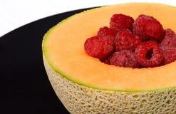 Cantaloupe e framboesas na placa Fotografia de Stock Royalty Free