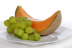 Cantaloupe and green grapes on white plate Stock Photos