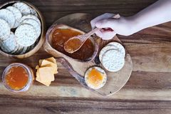 Cantaloupe Jam Appetizers. Overhead shot of a woman`s hand preparing Water cracker, cheddar cheese and homemade savory Salted Vanilla Cantaloupe jam appetizers stock photos