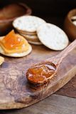 Cantaloupe Jam with Crackers and Cheese. Spoonful of homemade Salted Vanilla Cantaloupe jam with water crackers and cheddar cheese in the background stock image