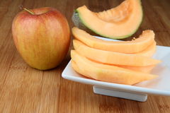 Cantaloupe melon. Sliced Cantaloupe melon on white plate and apple on wooden table Royalty Free Stock Photography