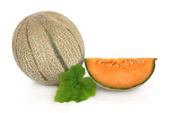 Cantaloupe Melon. Whole and with a slice with leaf sprig over white background stock photos
