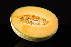 Cantaloupe melon fruit with reflection isolated on the black background Royalty Free Stock Images
