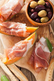 Cantaloupe melon with prosciutto grissini olives. italian appeti Royalty Free Stock Images