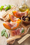 Cantaloupe melon with prosciutto grissini olives. italian appetizer.  royalty free stock photo