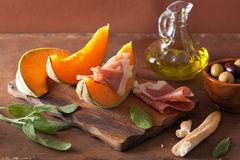 Cantaloupe melon with prosciutto grissini olives. italian appeti Royalty Free Stock Photos
