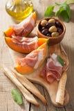 Cantaloupe melon with prosciutto grissini olives. italian appeti Stock Photo