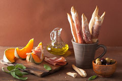 Cantaloupe melon with prosciutto grissini olives. italian appeti Stock Photography
