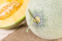 Cantaloupe melon with slice and leaves on burlap Royalty Free Stock Image