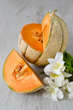Cantaloupe melon. On wooden background with a flower Royalty Free Stock Images