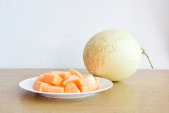 Cantaloupe Melon on wooden table. Cantaloupe Melon and plate on wooden table royalty free stock photos