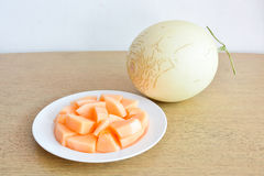 Cantaloupe Melon on wooden table. Cantaloupe Melon and plate on wooden table royalty free stock photography