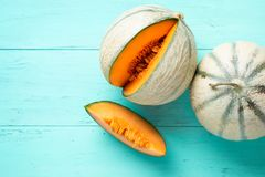 Cantaloupe melons on aquamarine background. Two cantaloupe melons and one slice on an aquamarine wooden planks. Top view royalty free stock images