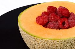 Cantaloupe and Raspberries on Plate. Cantaloupe and raspberries on decorative plate Royalty Free Stock Photography