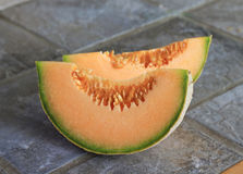 Cantaloupe Wedges. A cut up cantaloupe sitting on a slate tile kitchen counter top stock image